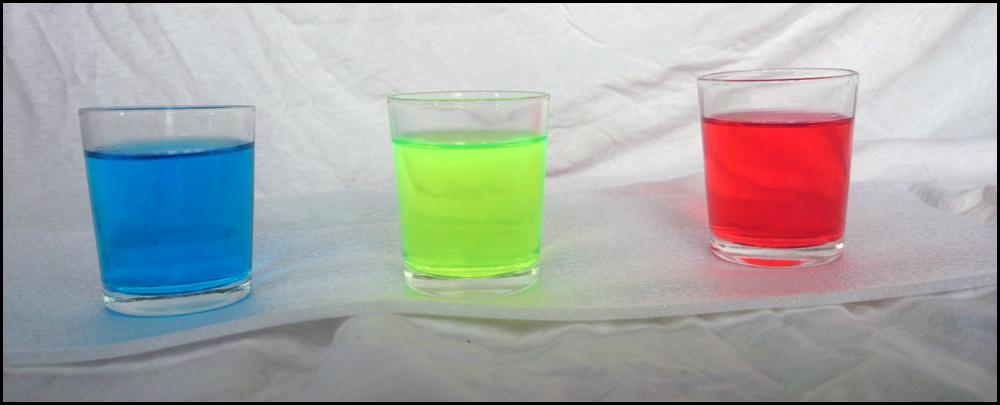 Ein Schnapsglas mit jeweils einem Tropfen Zusatz